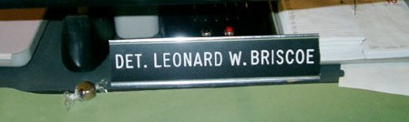 Photo: Desk-top nameplate reading 'Det. Leonard W. Briscoe.