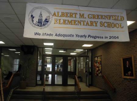 Photo: School hallway showing banner for Albert M. Greefield Elementary School: 'We made adequate yearly progress in 2004'.