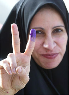 Photo: An Iraqi woman holds up her hand, and shows a purple finger, indicating    she has just voted, as she leaves a polling station in the centre of Az    Zubayr, Iraq. (AP/Andrew Parsons/Pool)
