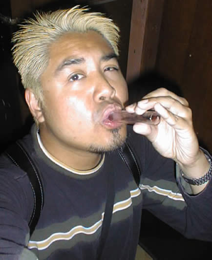 Photo: Joey deVilla, during the blonde-haired years, drinking bar shots out of a test tube. Taken July 2000.