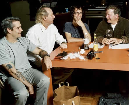 Photo: Henry Rollins, Adrian Belew, Ben Folds and William Shatner sitting at a table, presumably sometime during the recording of 'I Can't Get Behind That'.