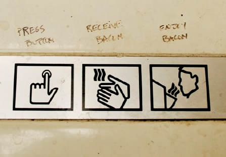 Photo: Hand dryer symbol instructions annotated with 'Press button. Receive bacon, Enjoy bacon.'
