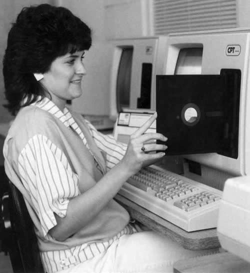 Photo: Woman inserting 8-inch floppy disk into drive of 1970s/1980s-era computer.