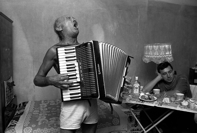 B&W photo of a man wearing only shorts playing accordion in a living room.